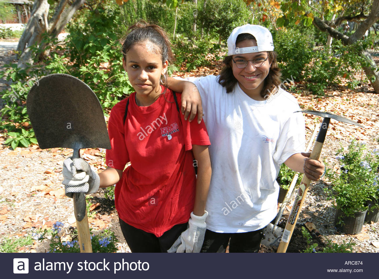 Miami Beach Florida Teen Job Corp Earth Day butterfly garden installation digging planting working work - Stock Image
