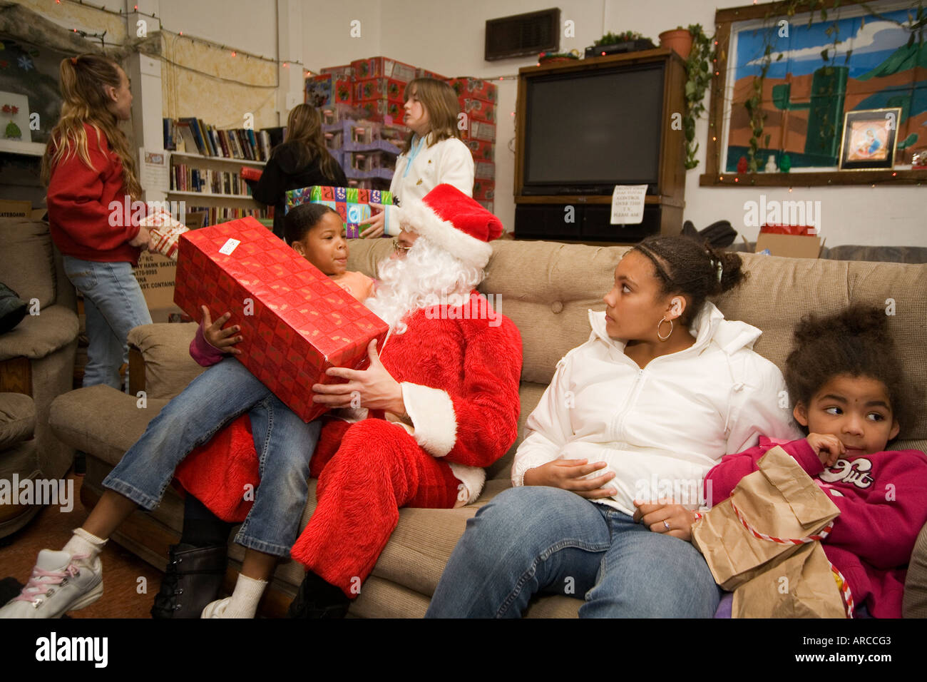 A volunteer Santa Claus distributes donated Christmas gifts to low ...