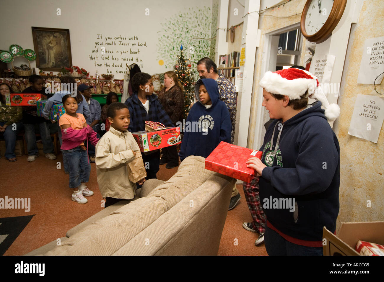 A Santa Claus hatted volunteer distributes donated Christmas gifts ...