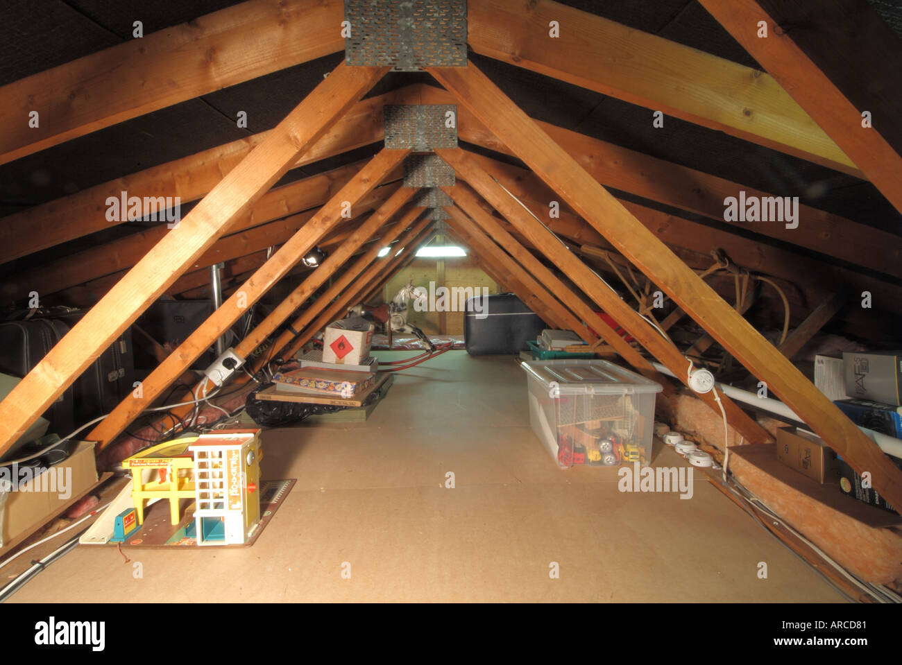Domestic dwelling loft space low roof pitch showing timber roof trusses and mdf boarding to centre gangway for storage access & Domestic dwelling loft space low roof pitch showing timber roof ...