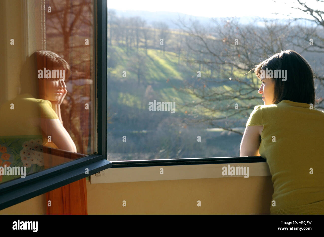 Young woman looking out of a window at a countryside view - reflected in the glass, rear view Stock Photo