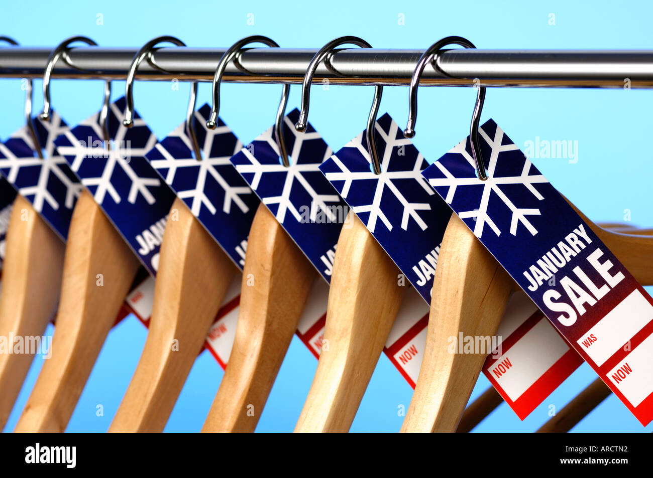 Row of wooden coathangers with January Sale price tags - Stock Image