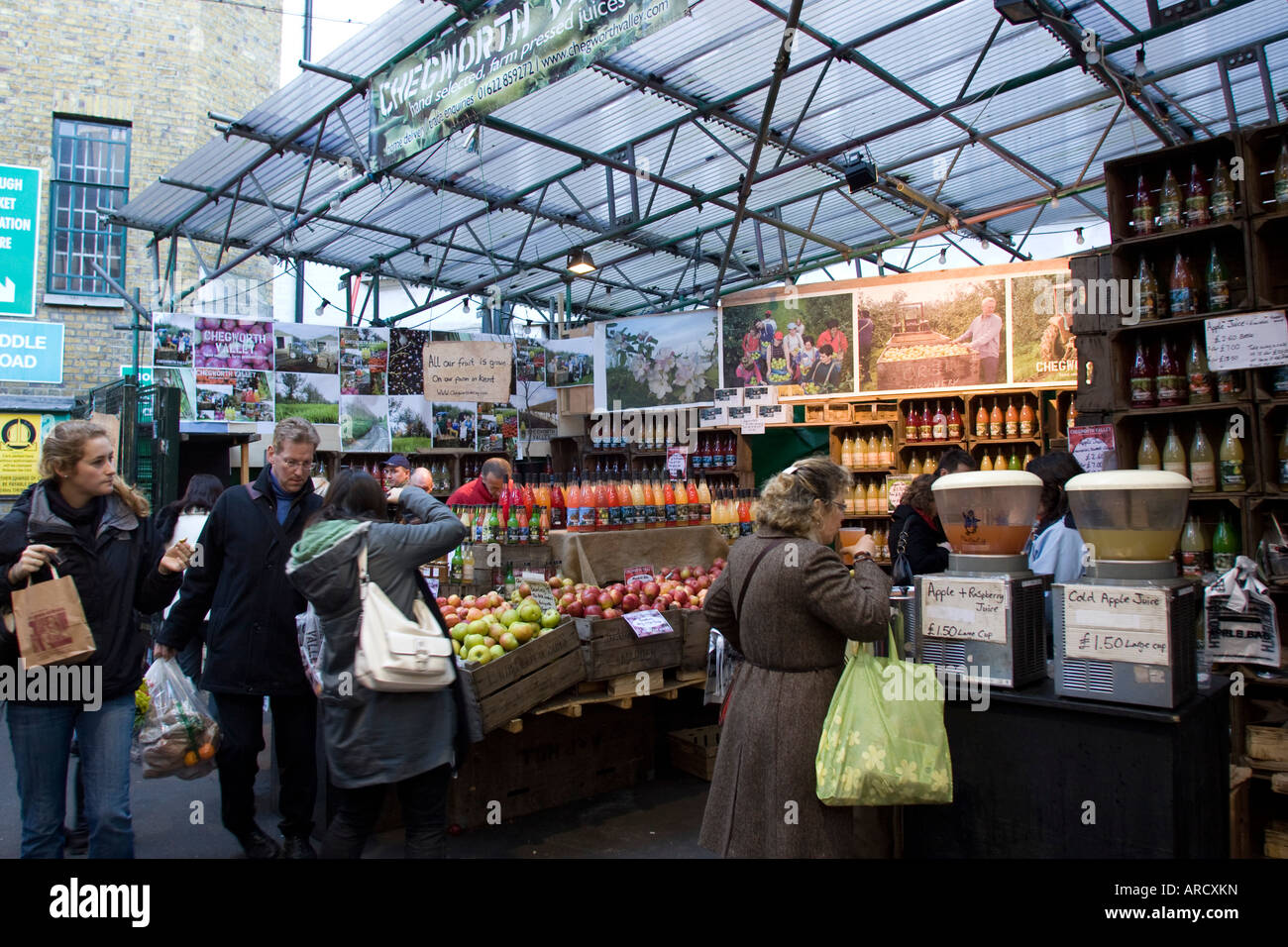 Customers at Stall selling fruit and juices at Borough Market Southwark London GB UK - Stock Image