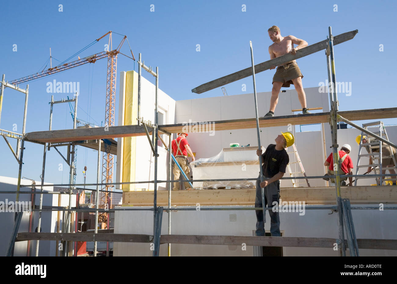 Scaffolders At Work On A Prefabricated House Construction Site