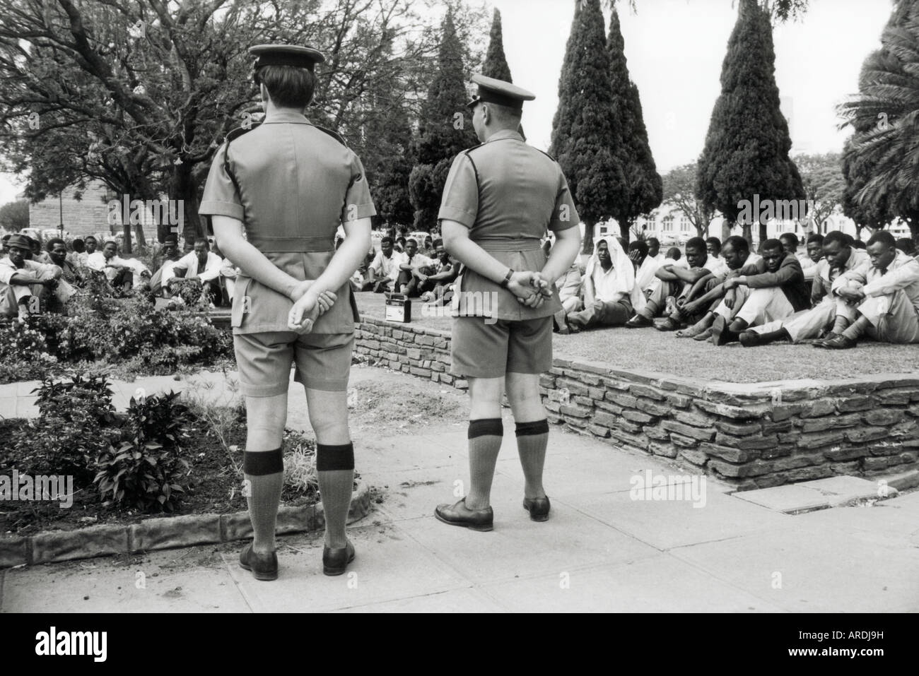 Policemen watch silent crowds in Cecil Square Salisbury Rhodesia. later Harare Zimbabwe, on 11 November 1965, as - Stock Image