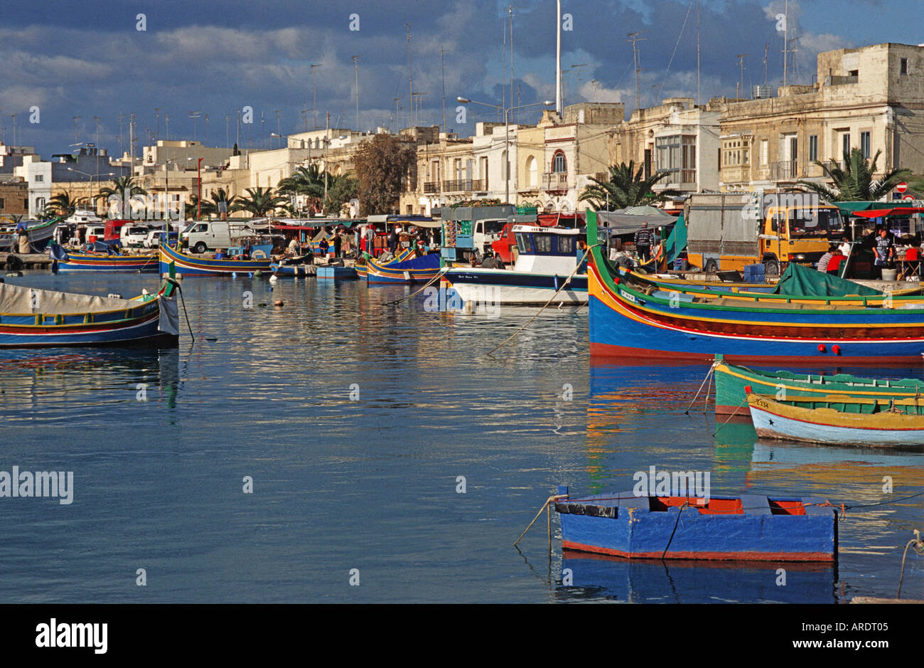 Traditional Maltese fishing boats called Luzzus moored in Marsaxlokk harbour Malta - Stock Image