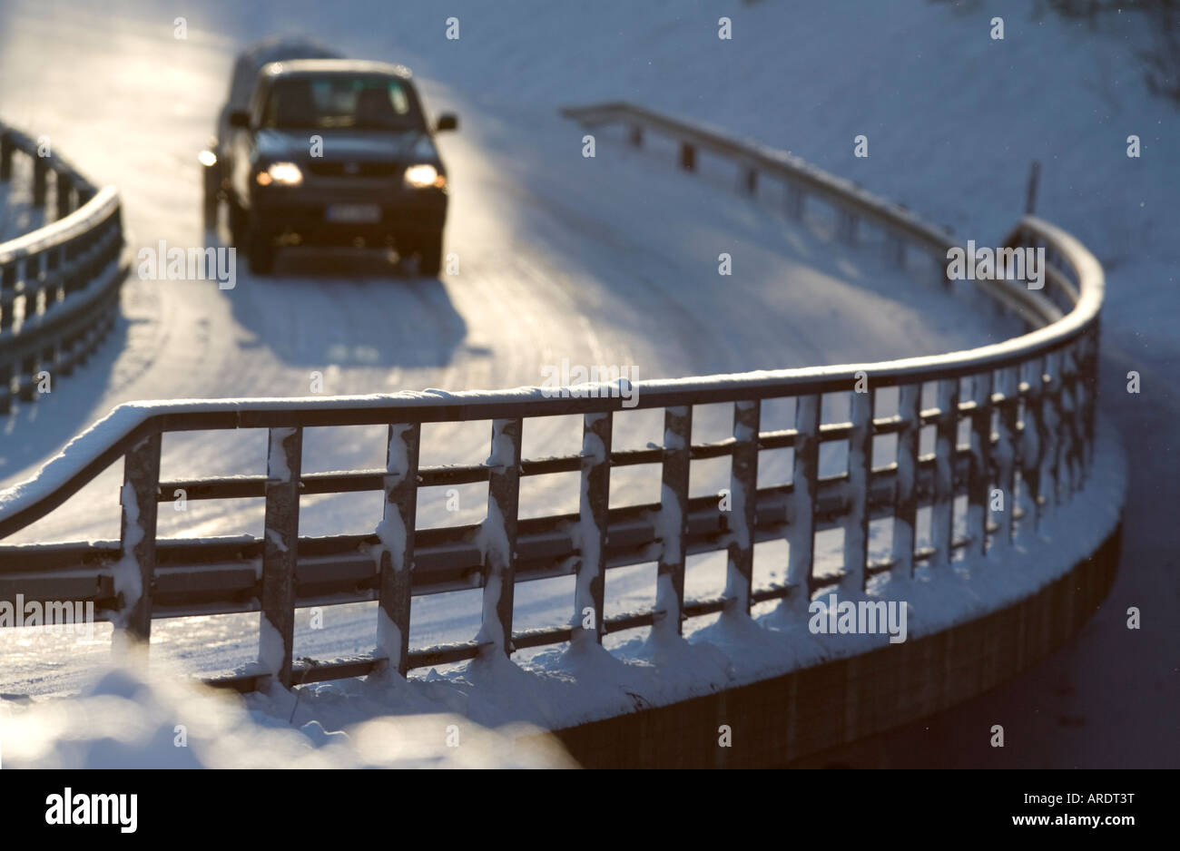 Metallic snowy road bridge railing and car driving on the road at Winter , Finland Stock Photo