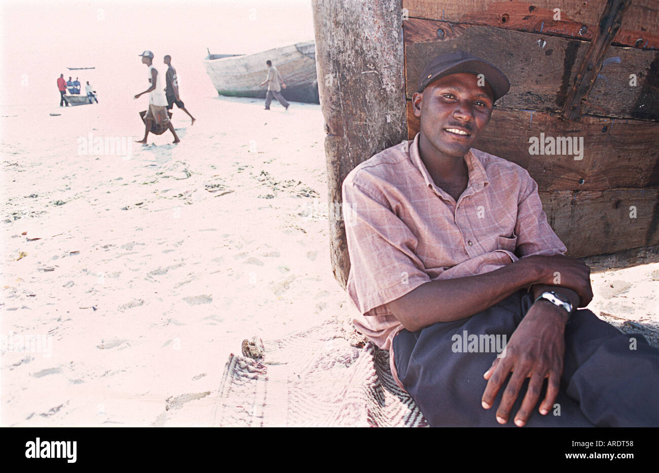 Tanzanian man photographed sitting beside a beached dhow at the fish market in Dar es Salaam Tanzania East Africa - Stock Image