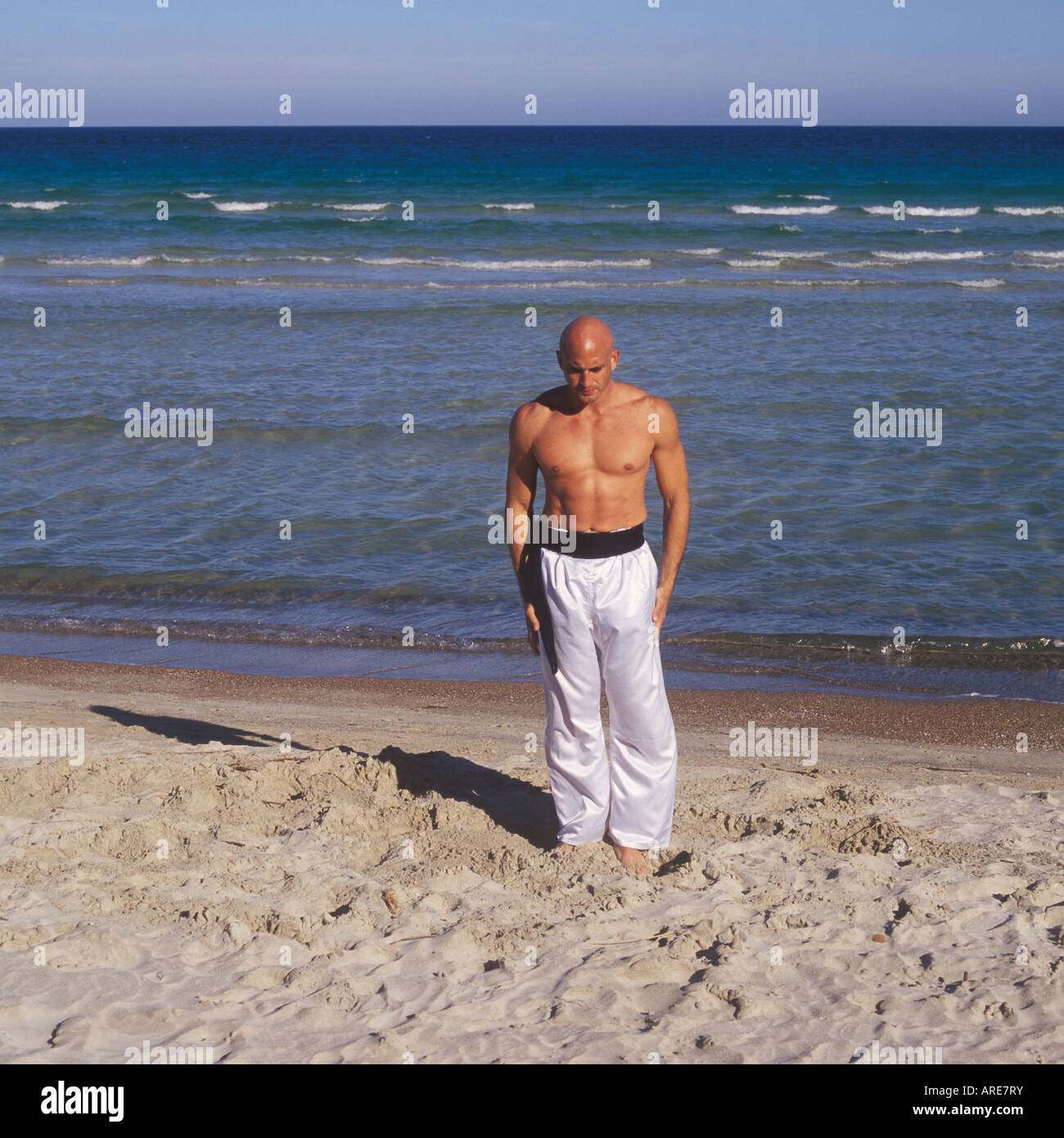 Professional Tai Chi and Kong Fu instructor undertaking workout on beach in Mallorca, Balearic Islands, Spain. - Stock Image