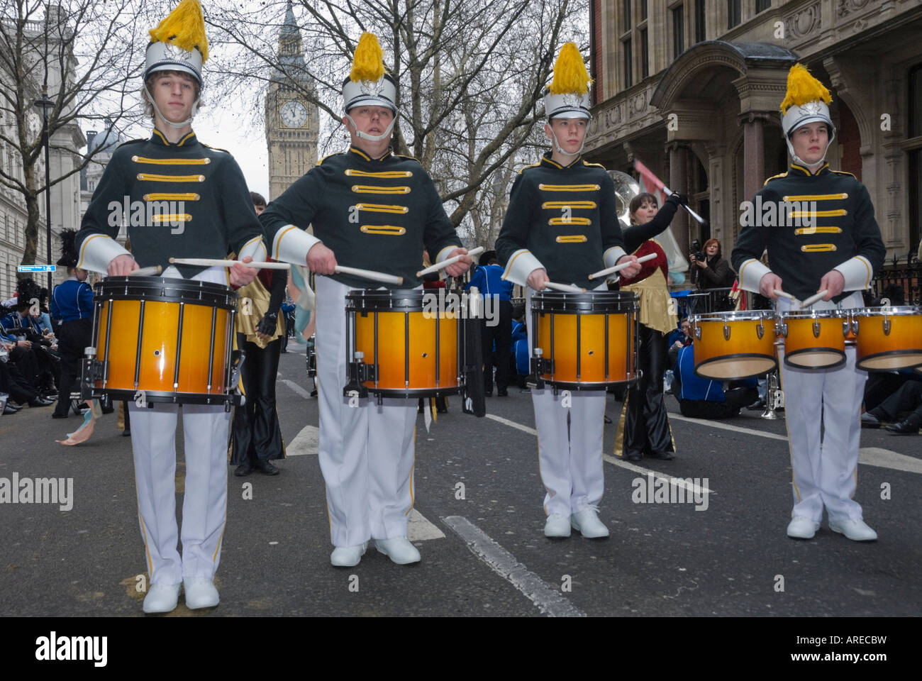 Four drummers from a US High School marching band form a line with Big Ben behind them in London New Year Parade. Stock Photo