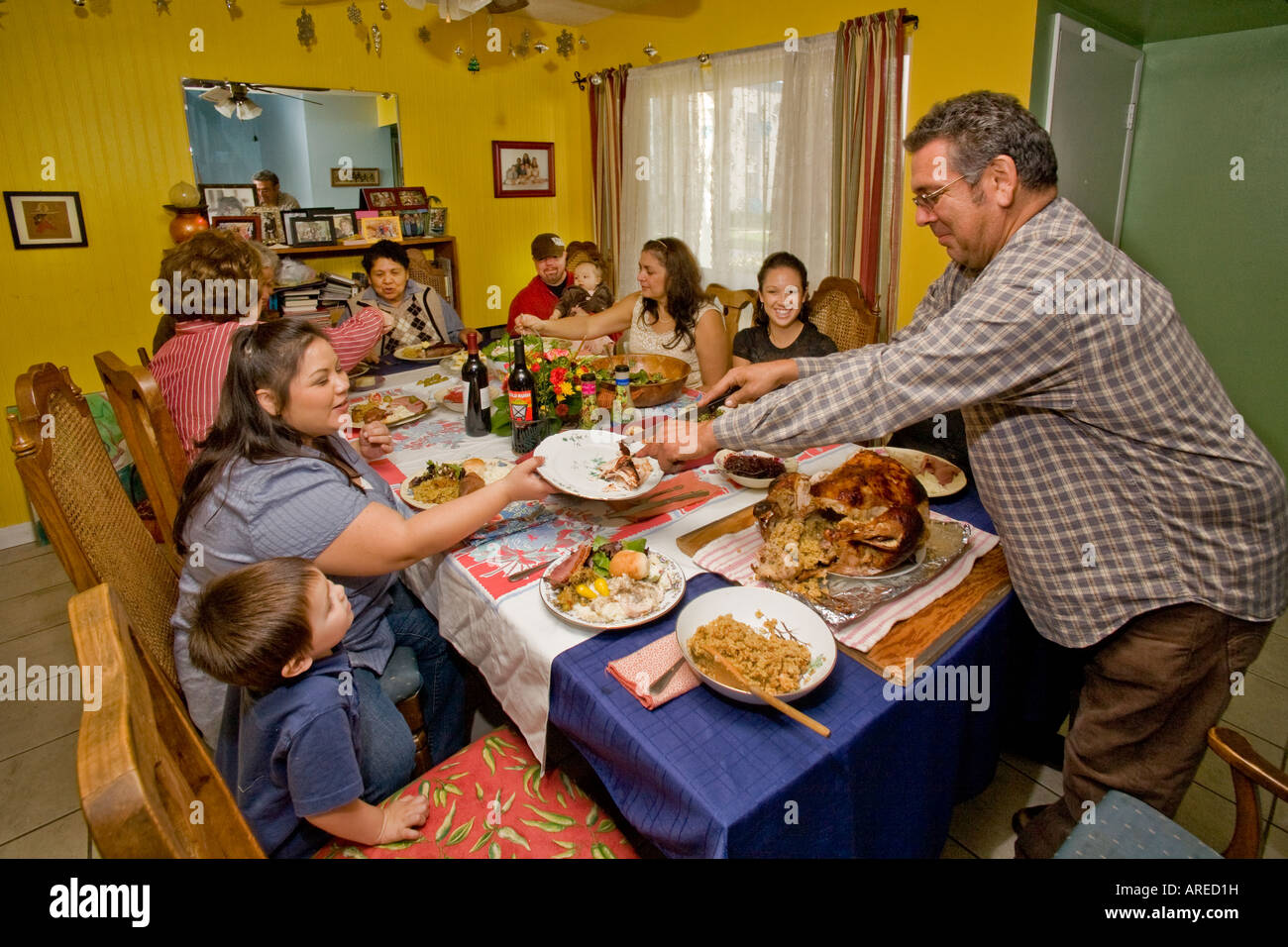 A Hispanic father carves the turkey at a Thanksgiving dinner - Stock Image