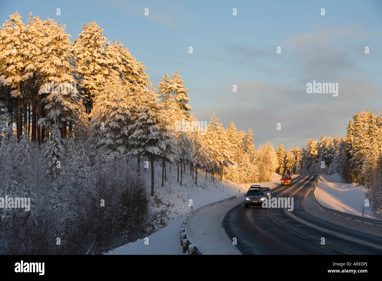 Cars driving on Finnish highway at evening light at Winter Finland - Stock Image
