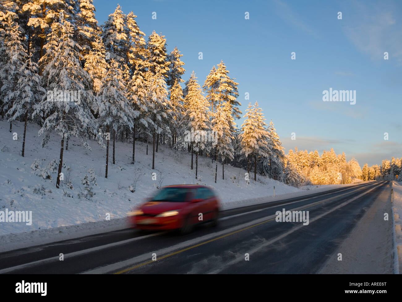Car driving on Finnish highway at evening at Winter Finland - Stock Image