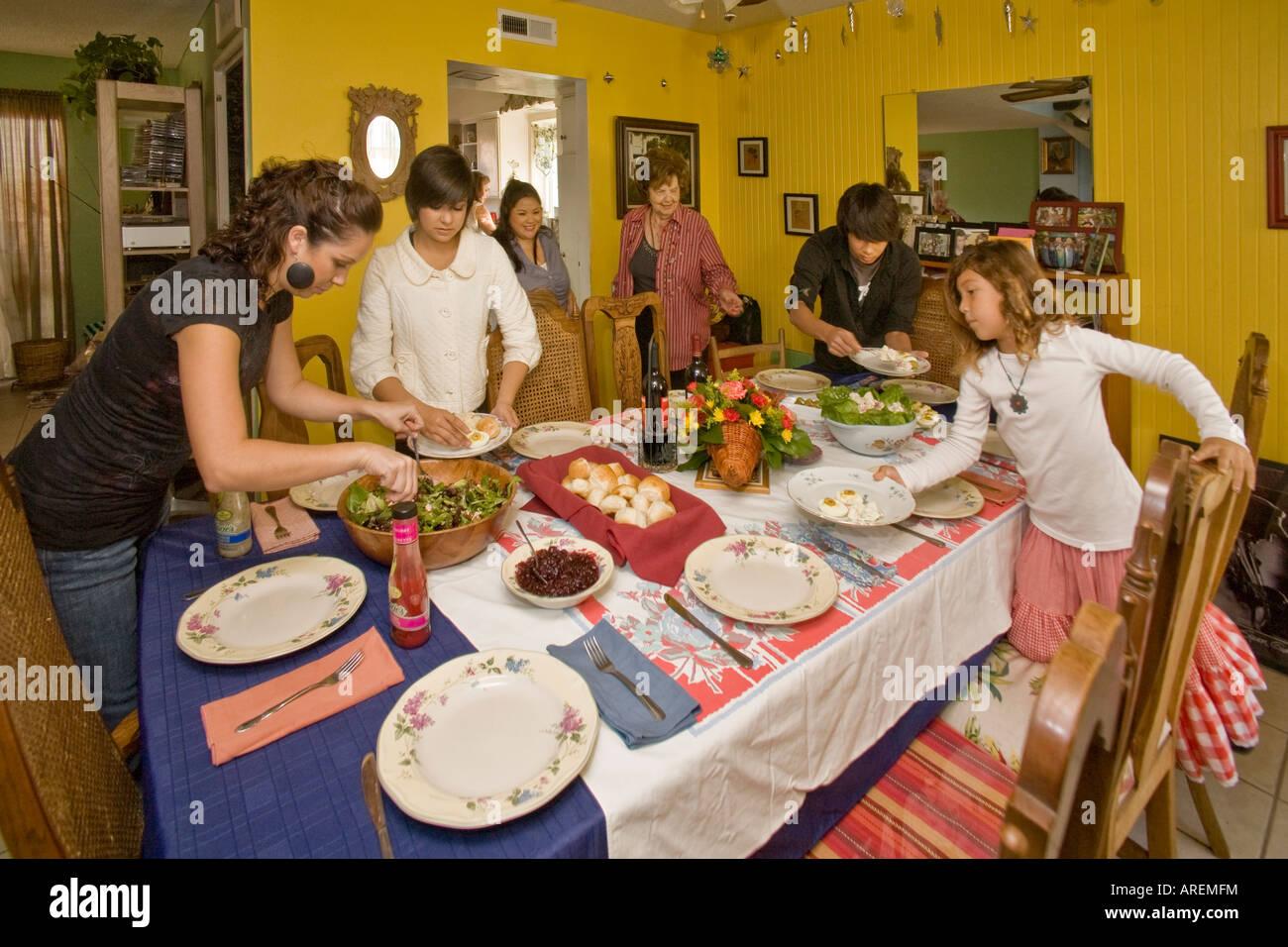 Members of an extended Hispasnic Caucasian family prepare the dining table before Thanksgiving dinner in California - Stock Image