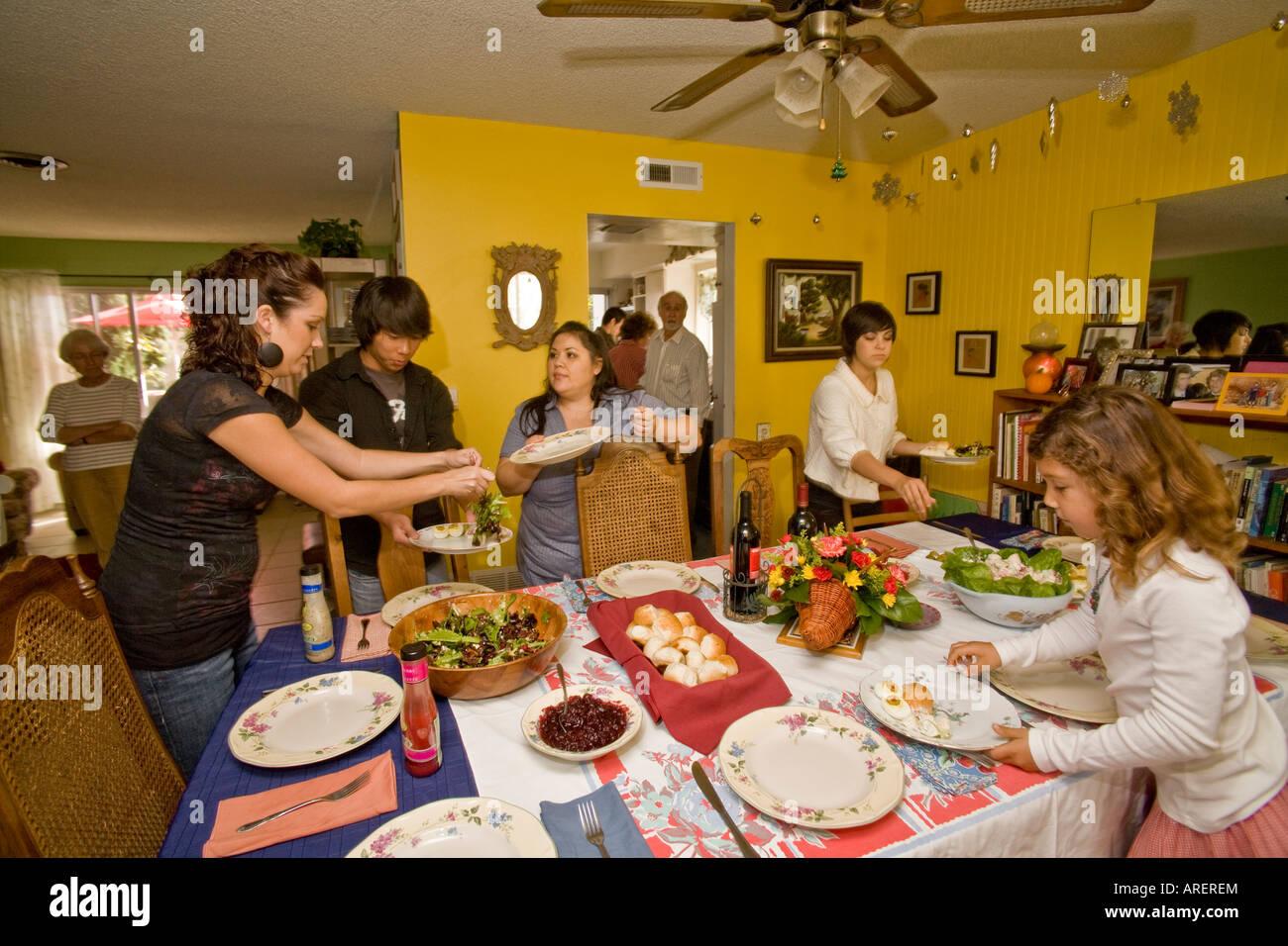 Members of an extended Hispasnic Caucasian family start serving Thanksgiving dinner - Stock Image