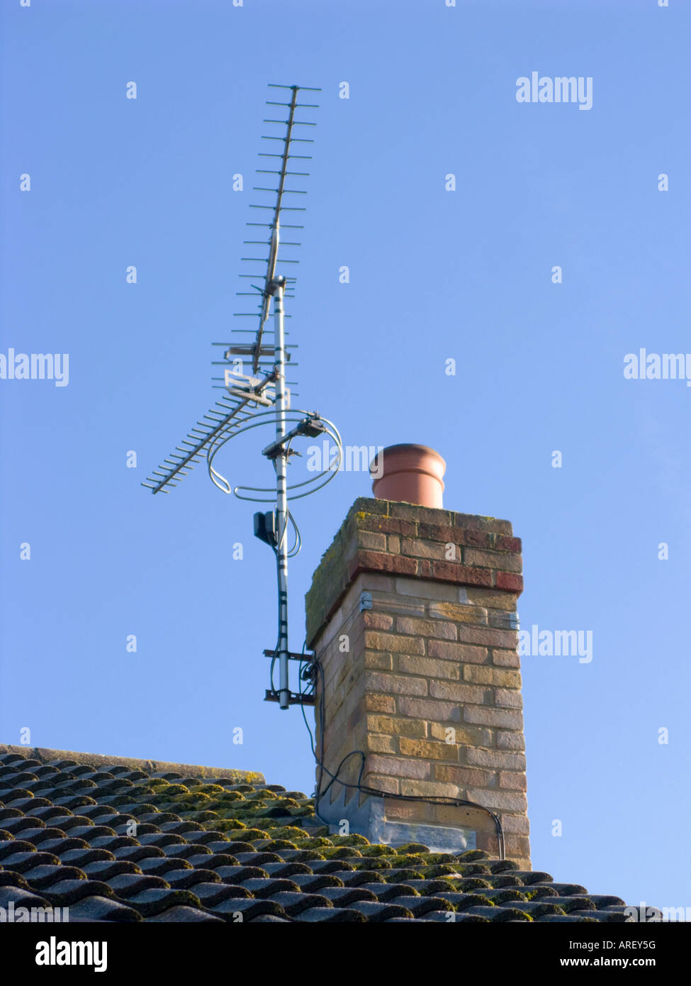 colour image looking up to a roof and  chimley which has a tv aerial attached to it, clear blue sky Stock Photo