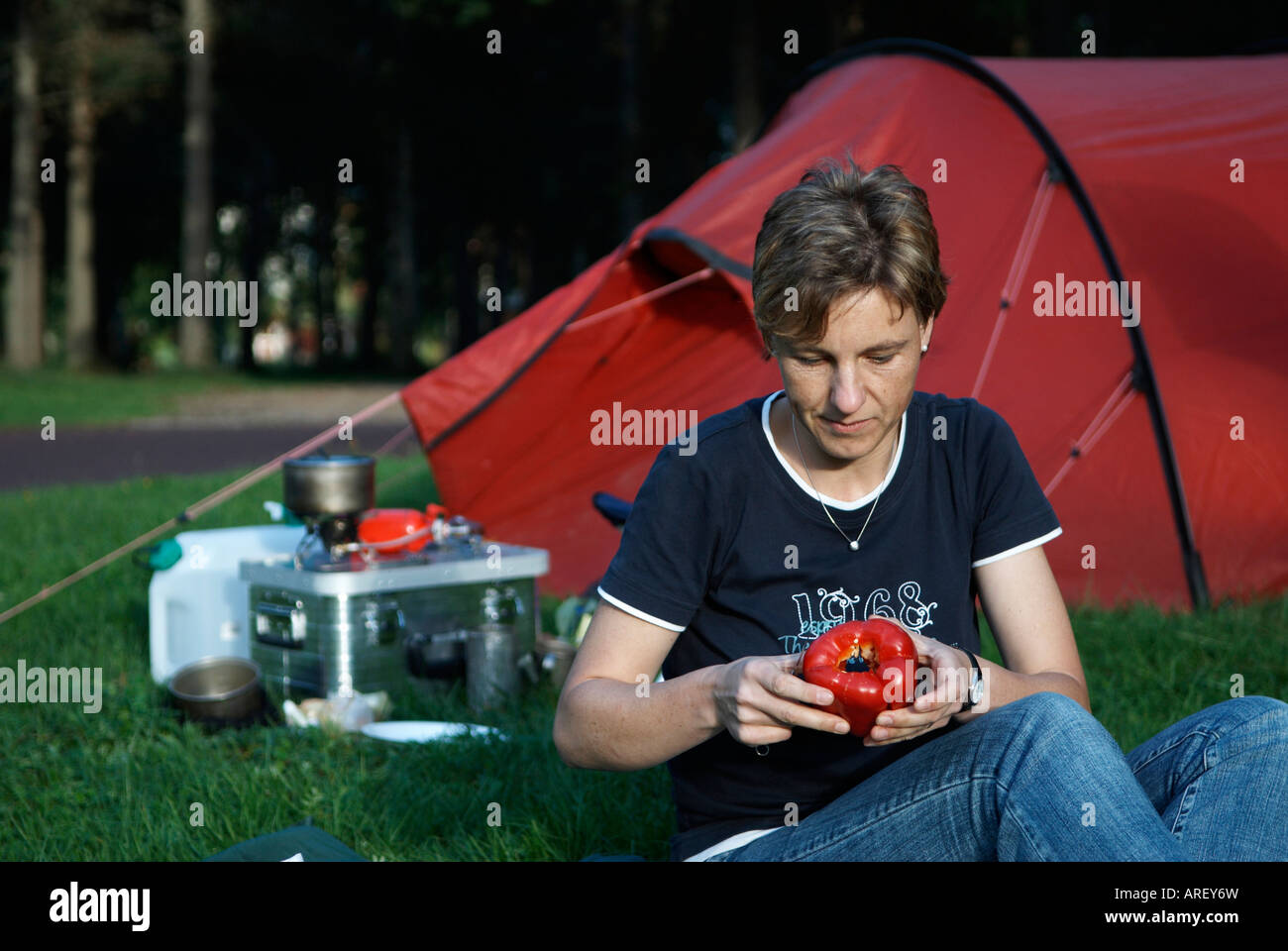 A woman preparing a meal in front of a red tent and some cooking equipment Mora Dalarna Sweden August 2007 - Stock Image