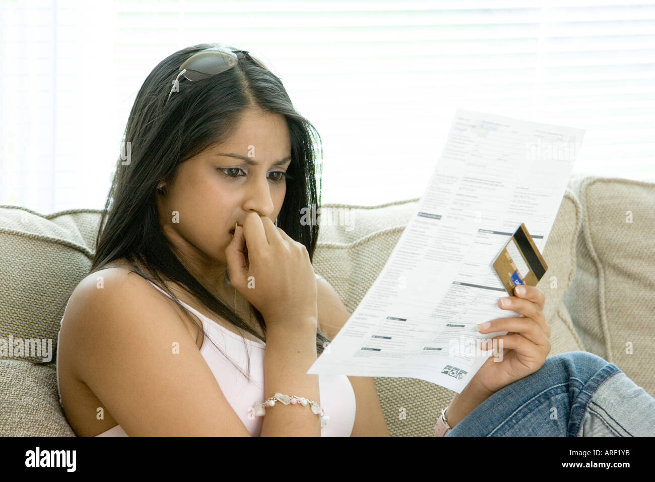 A young woman shocked by her credit card bill - Stock Image