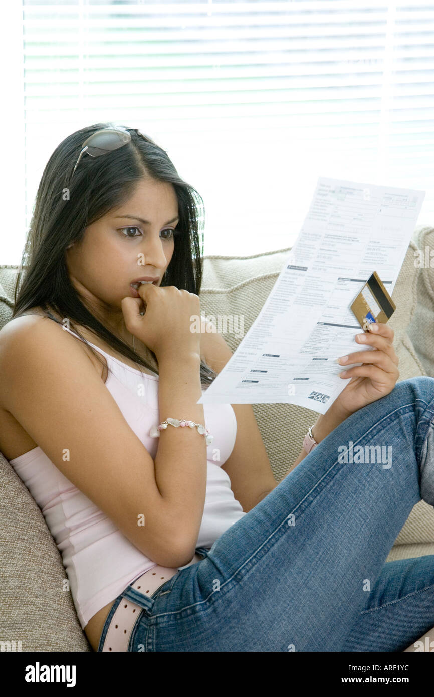 A young woman shocked by her credit card statement - Stock Image