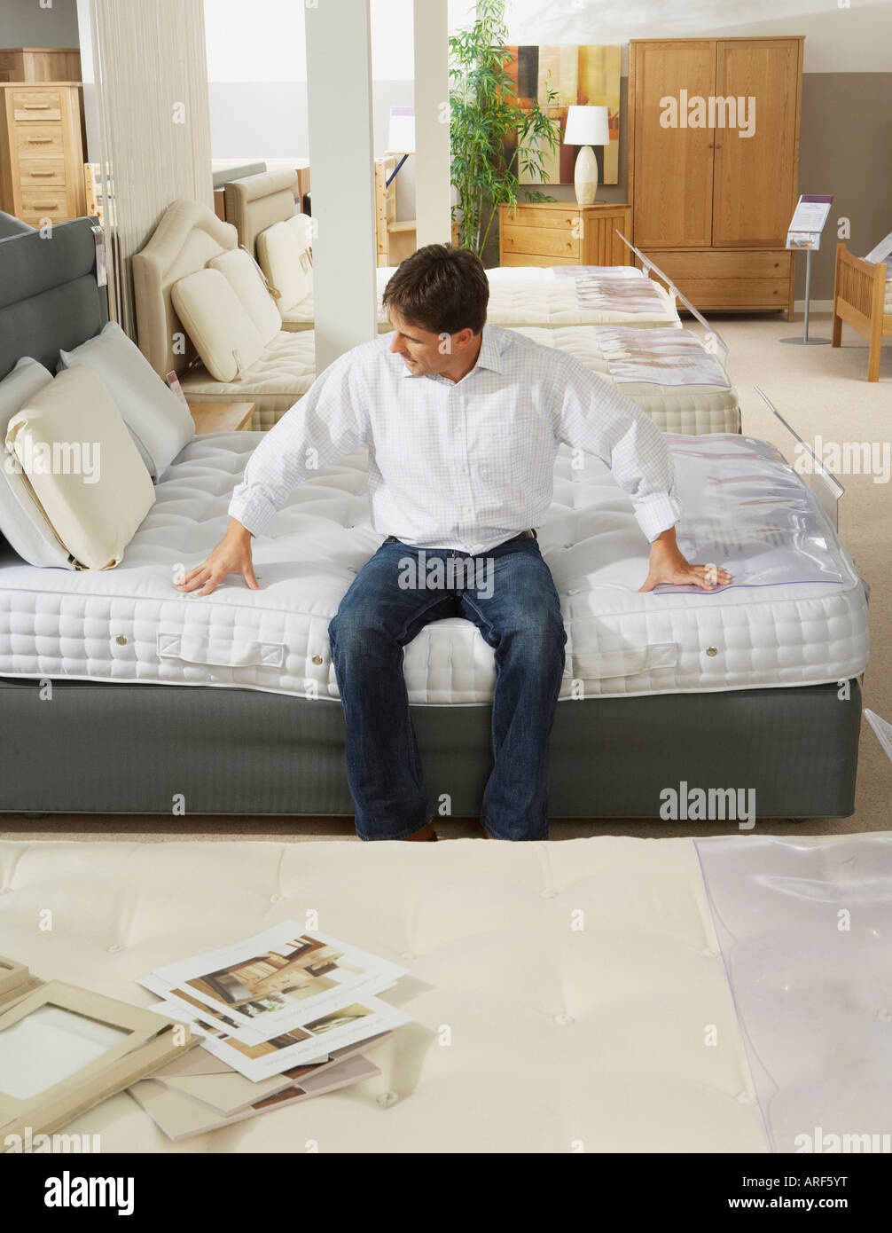 Man Sitting On Bed In Furniture Store   Stock Image