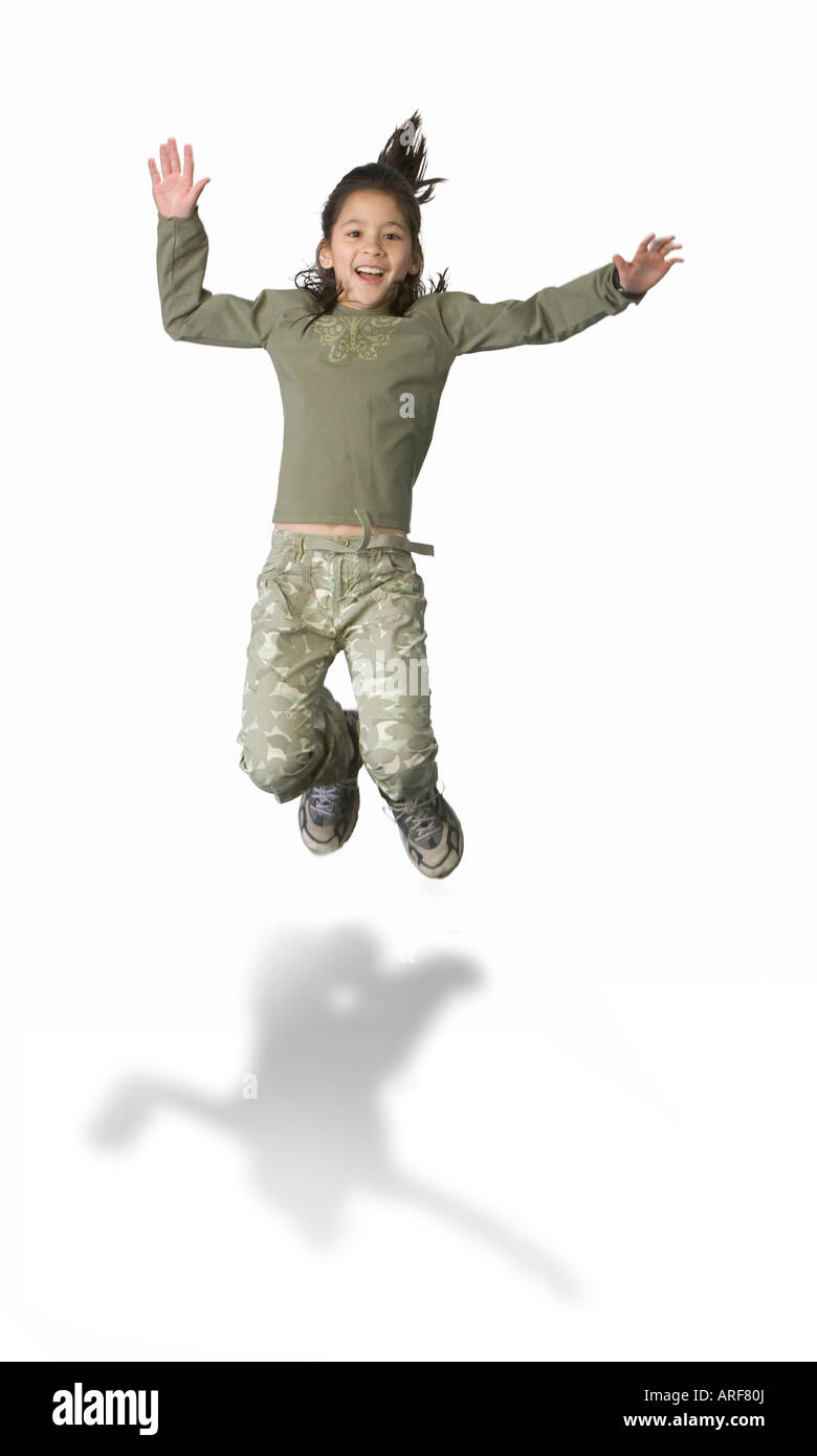 Pre teen Latino girl jumping for joy - Stock Image