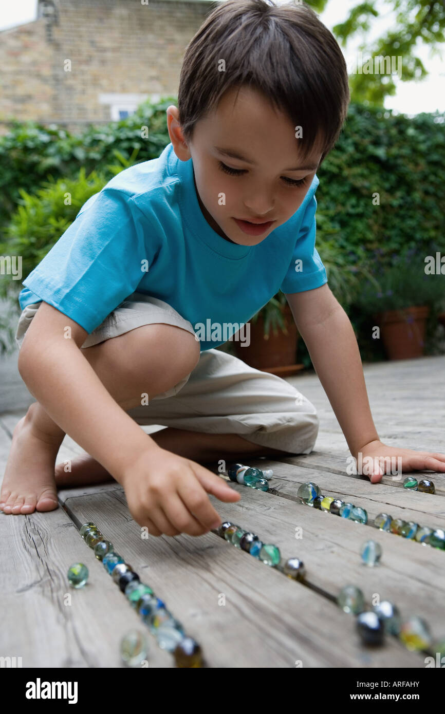 Portrait of a boy playing marbles - Stock Image