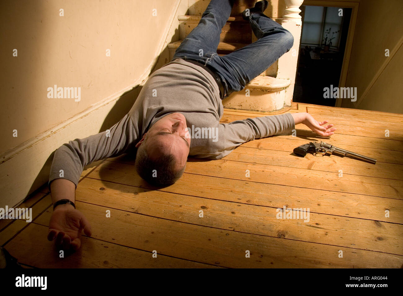 Body of dead man lying on the floor at the bottom of stairs with a handgun  by his side