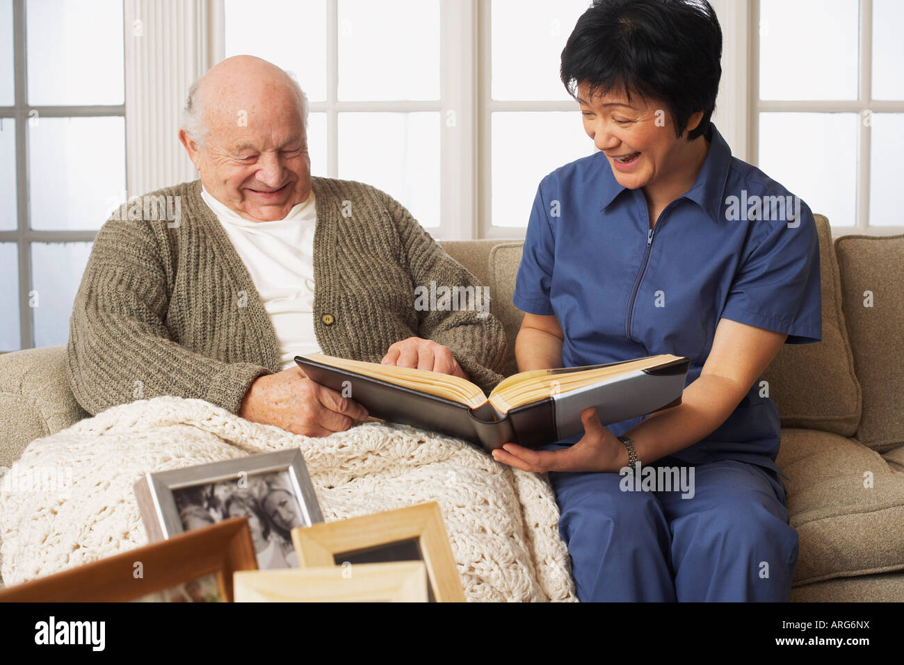 Senior Man with Woman Looking at Pictures Together Stock Photo