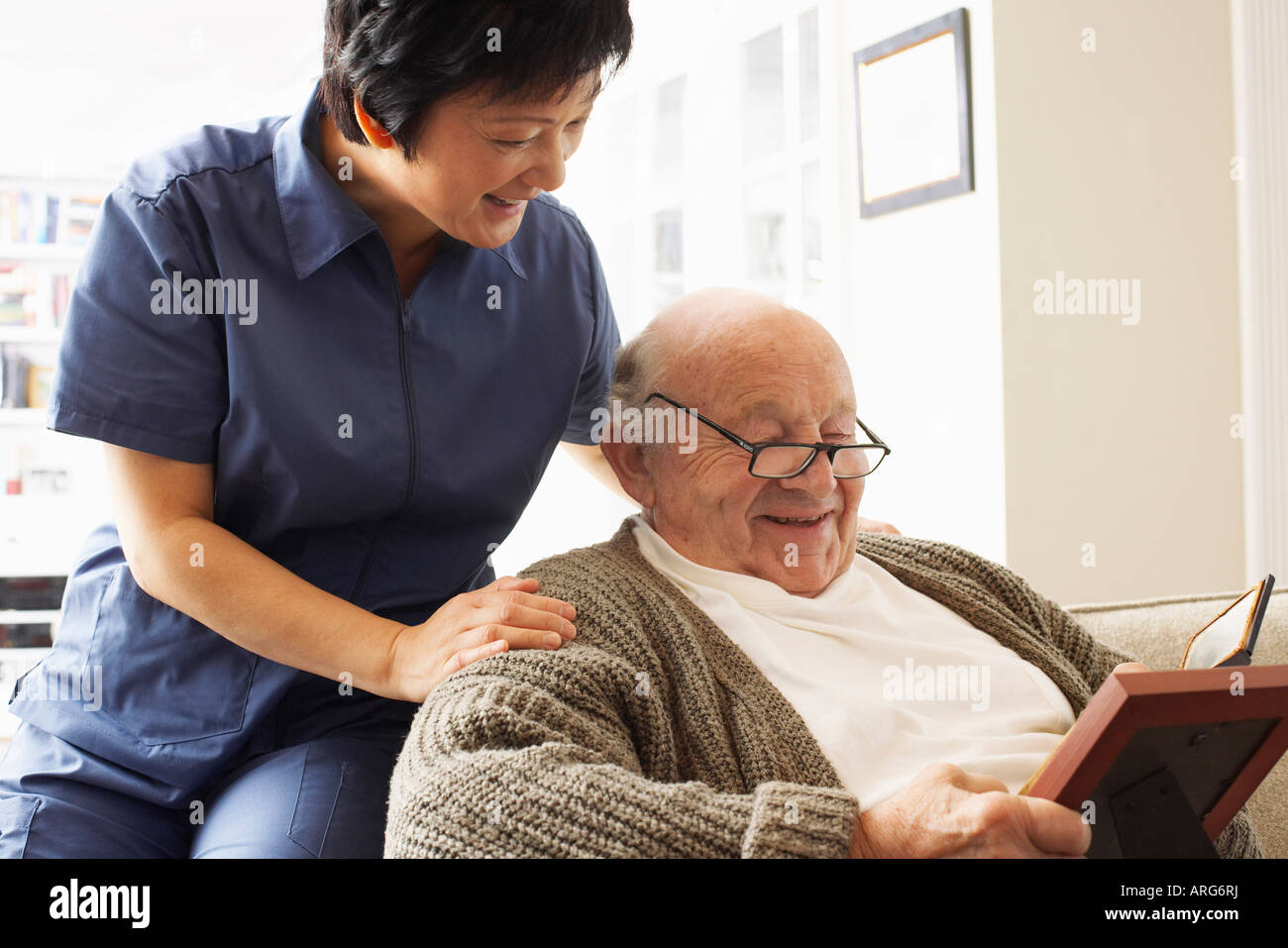Senior Man Looking at Pictures with Woman Looking over his Shoulder Stock Photo