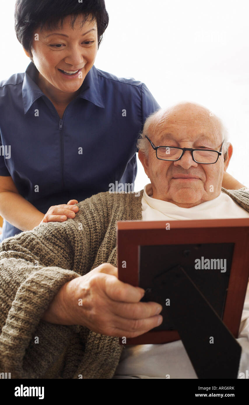 Senior Man Looking at Picture with Woman Looking over his Shoulder Stock Photo