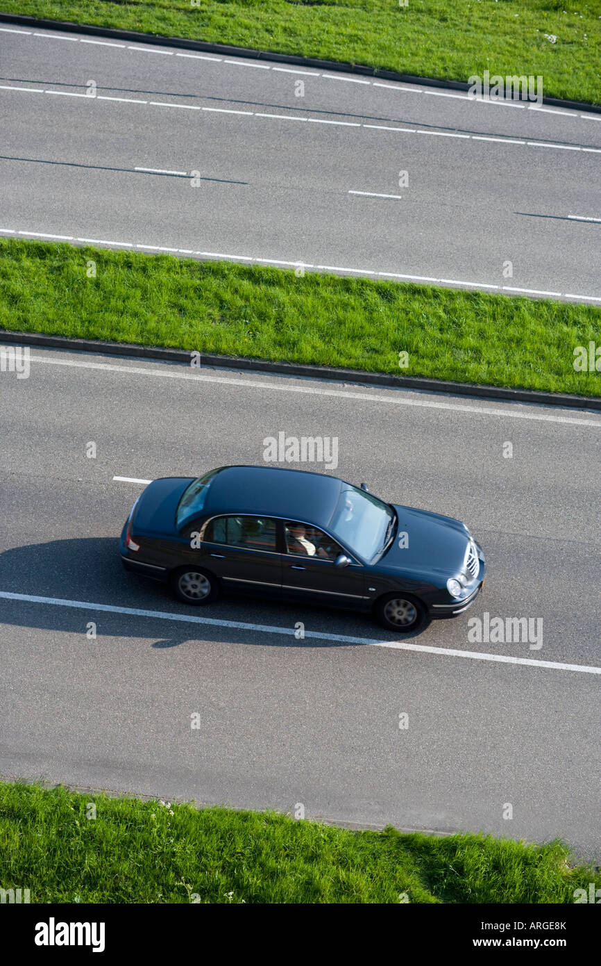 Aerial view of a car driving on a dual carriageway motorway highway in Europe. The Netherlands. - Stock Image