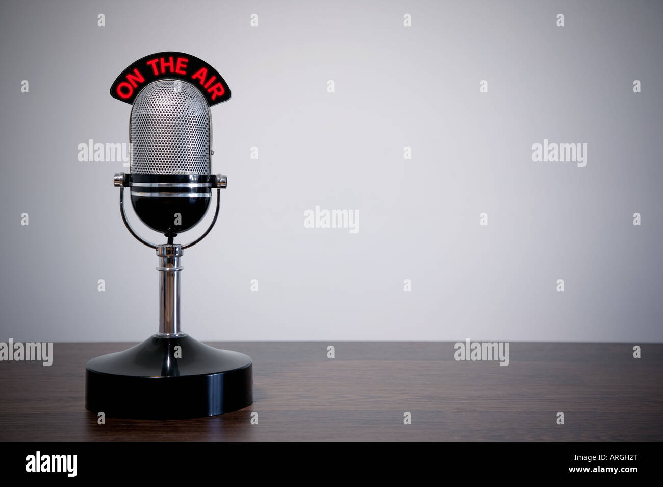 Retro microphone with an On the Air illuminated sign on a desk vignetted background - Stock Image
