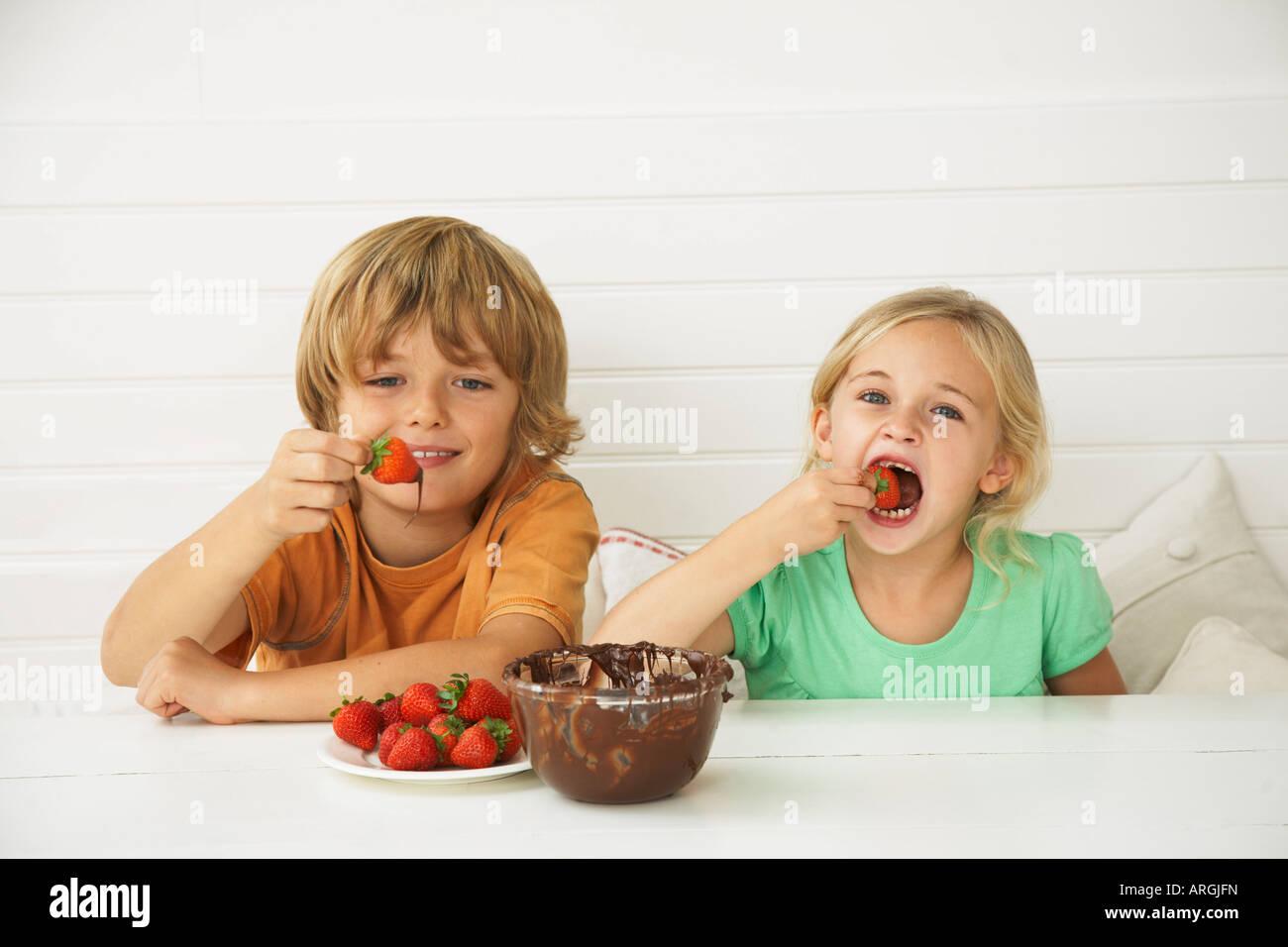Children Eating Strawberries and Chocolate Stock Photo