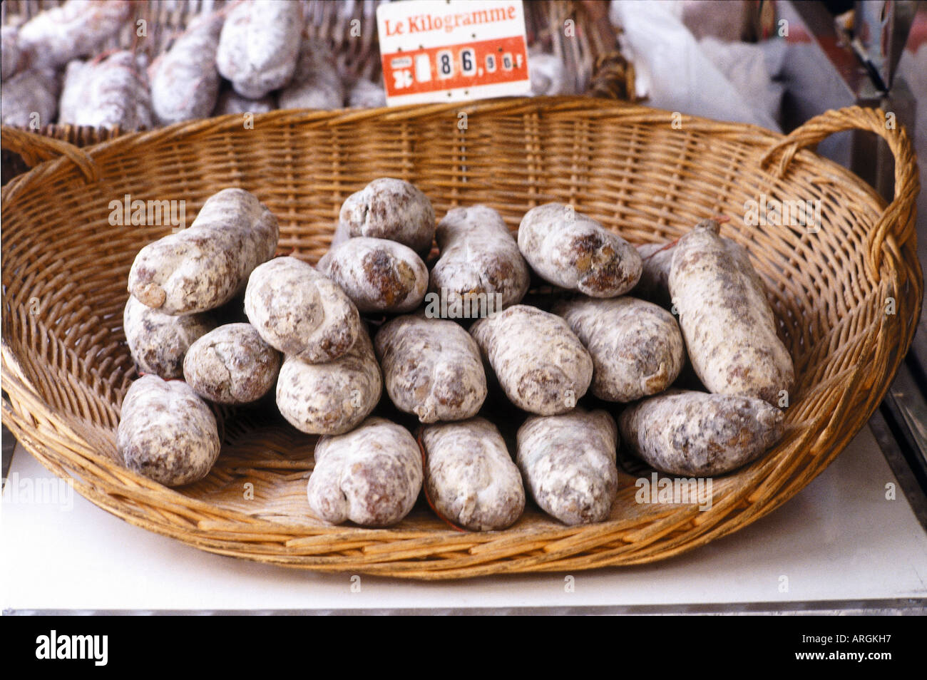 A basket of dry sausages with their price tag per kilogram in the town of Anzy le Duc - Stock Image