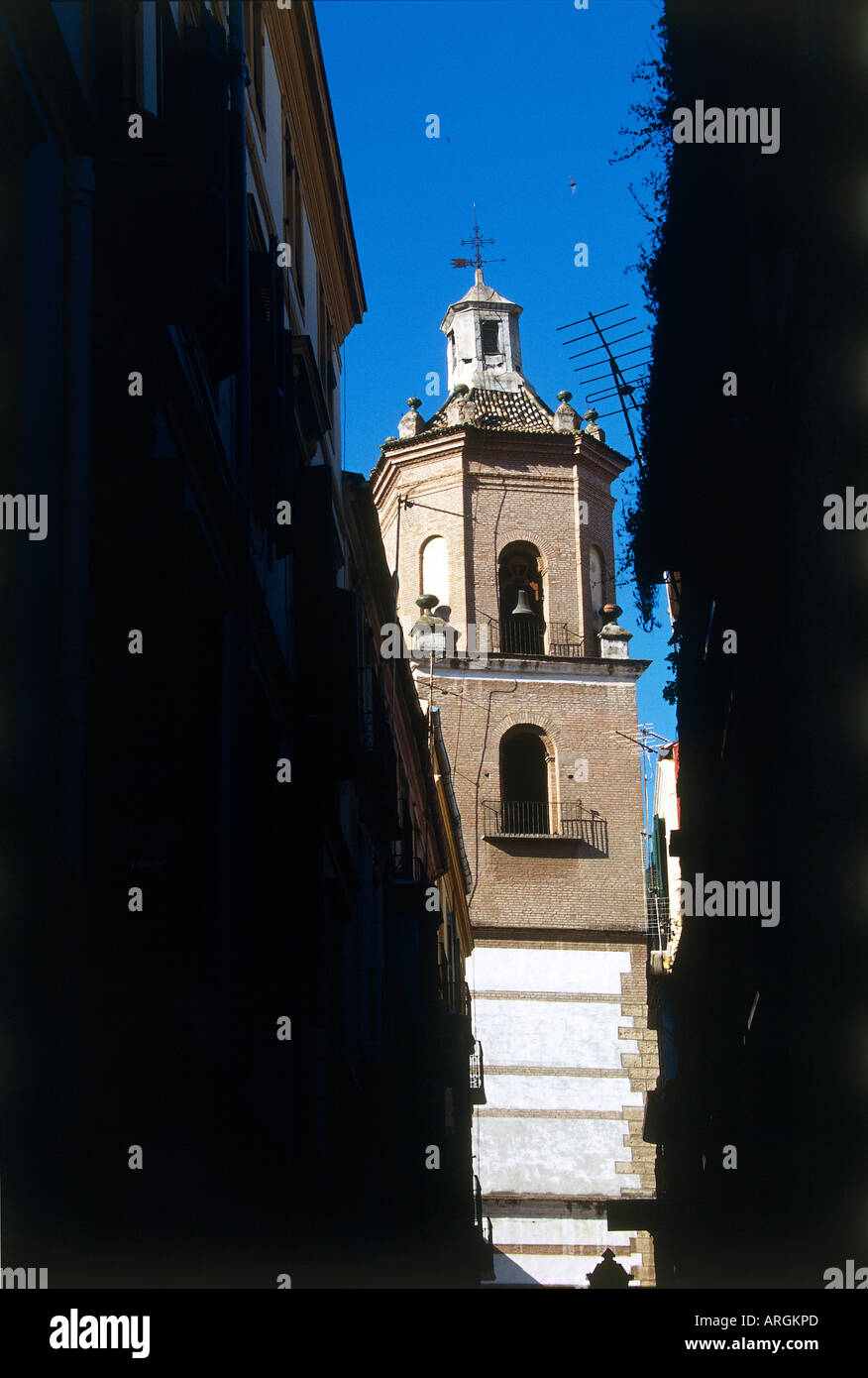 Seen from a sun shaded narrow street the Iglesia de Los Martires translates as the Church of the Martyrs - Stock Image