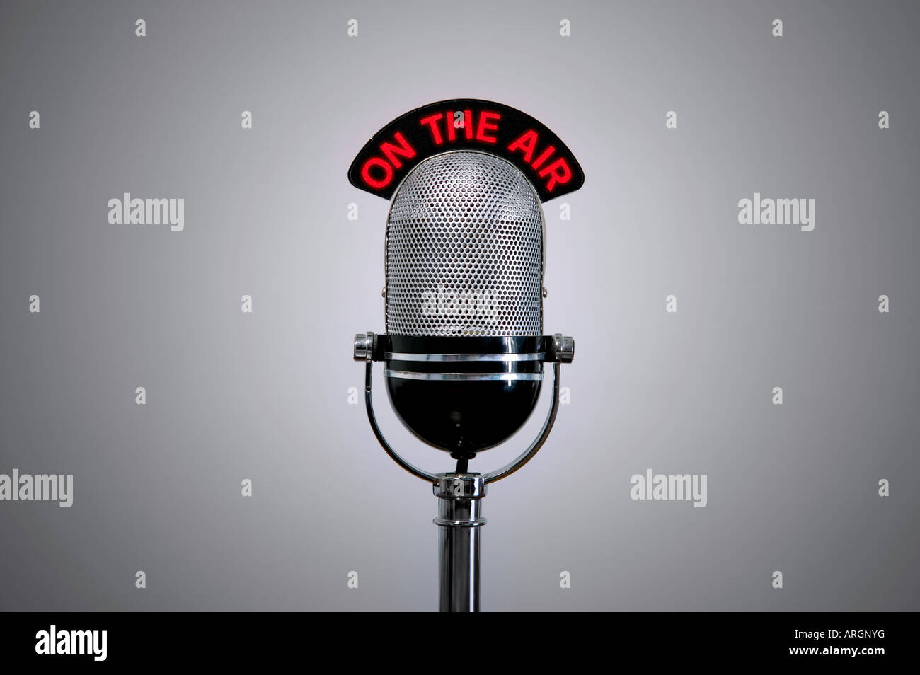 Old retro microphone with illuminated On the Air sign - Stock Image
