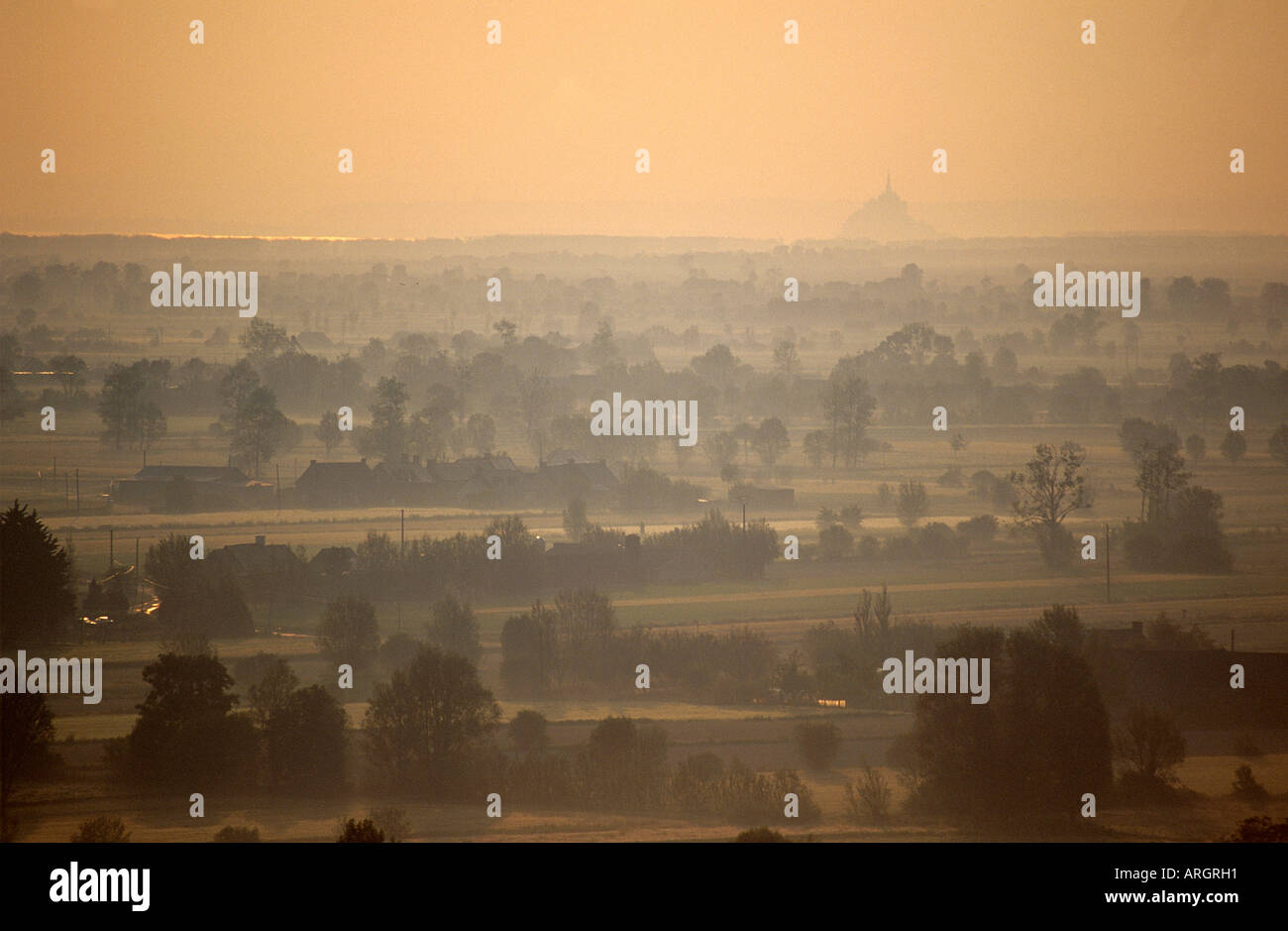 The sea and distinctive shape of the Mont St Michel viewed from Mont Dol through a mist softening the patchwork Stock Photo