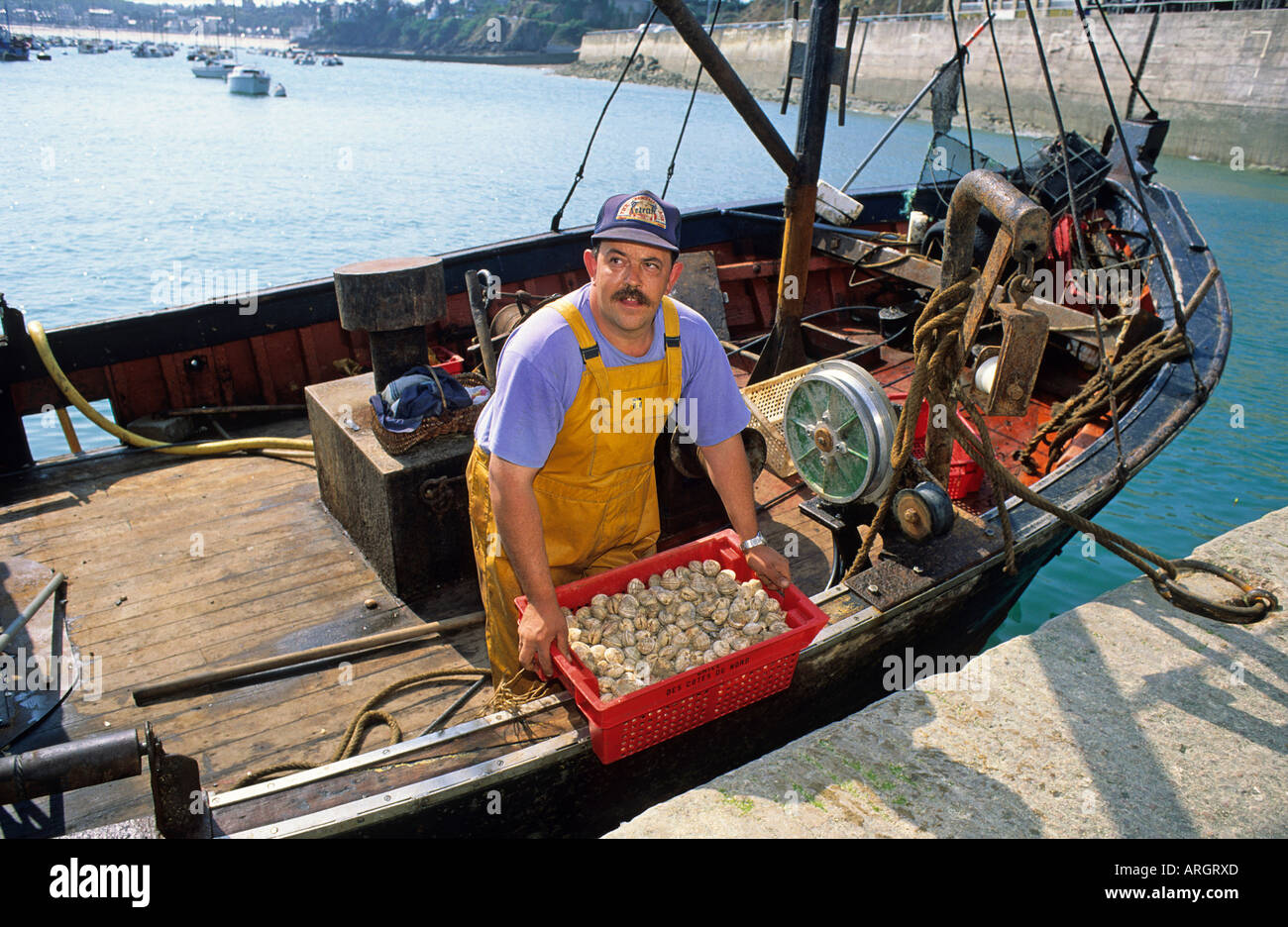 A fisherman unloading his catch onto the quayside from the decks of his boat tied up in the harbour of St Cast Le Guildo - Stock Image