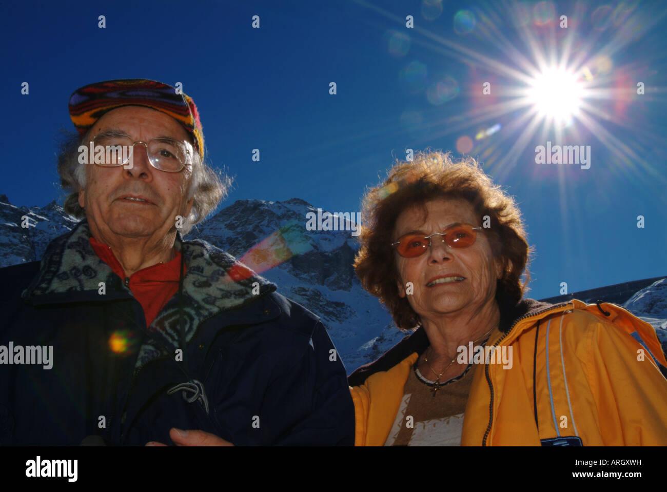 Senior couple, sun, mountains, snow. - Stock Image