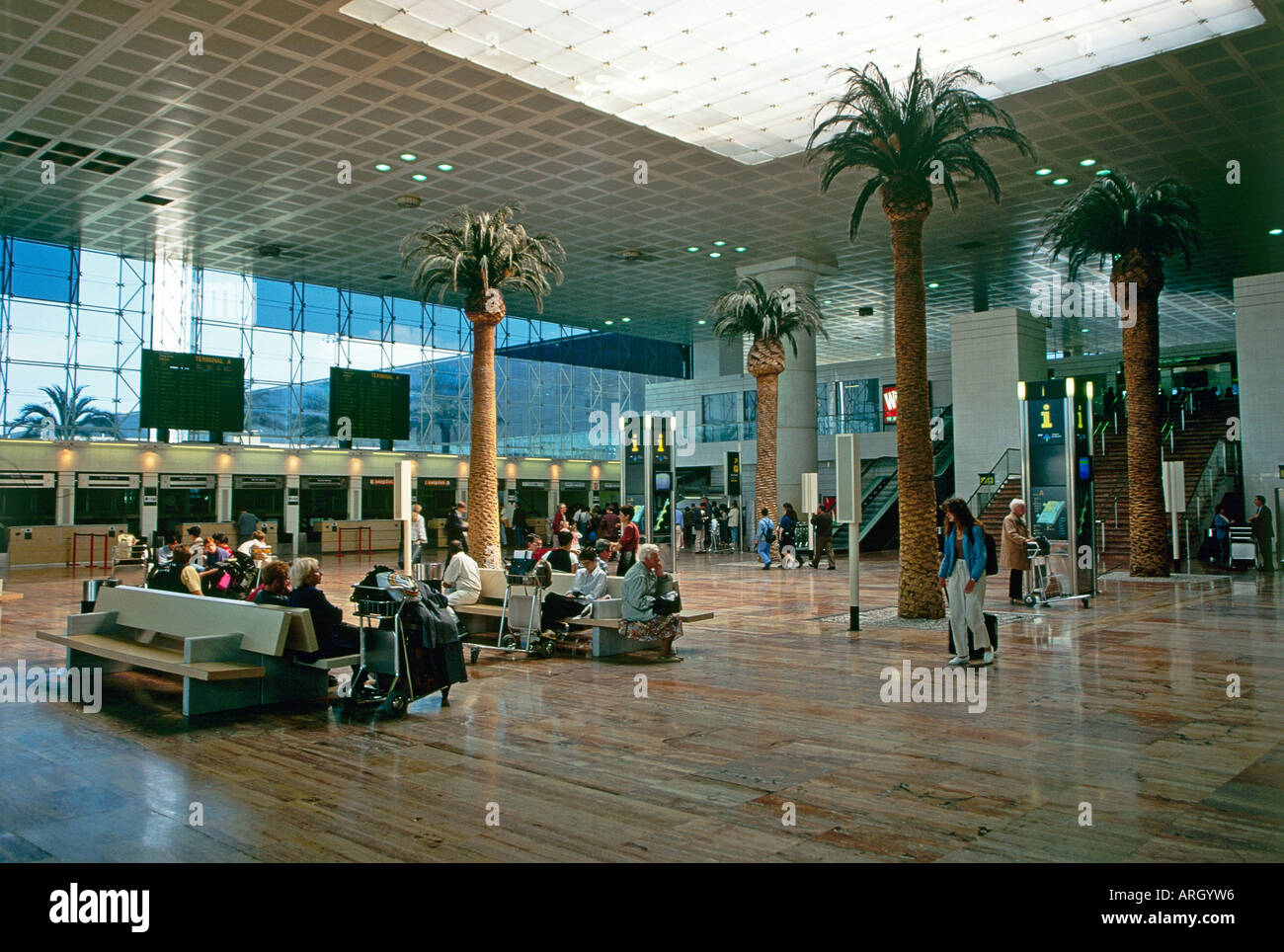 A number of passengers sitting in the departure lounge of Barcelona s international airport El Prat de Llobregat decorated with towering indoor palms which rise up from the polished wood effect floor - Stock Image