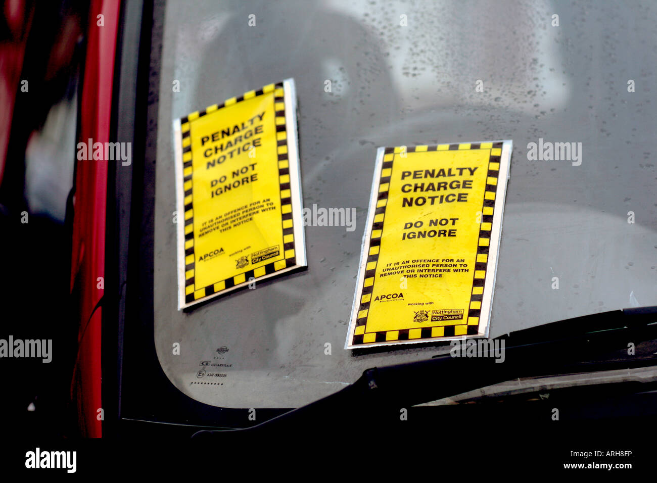 Parking Tickets. Penalty Charge Notices.  Not one but two parking tickets fixed to the window of a parked vehicle. - Stock Image
