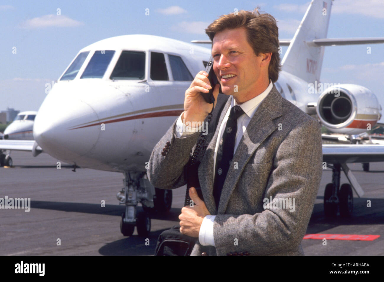 Businessman on global satellite phone in front of corporate jet - Stock Image
