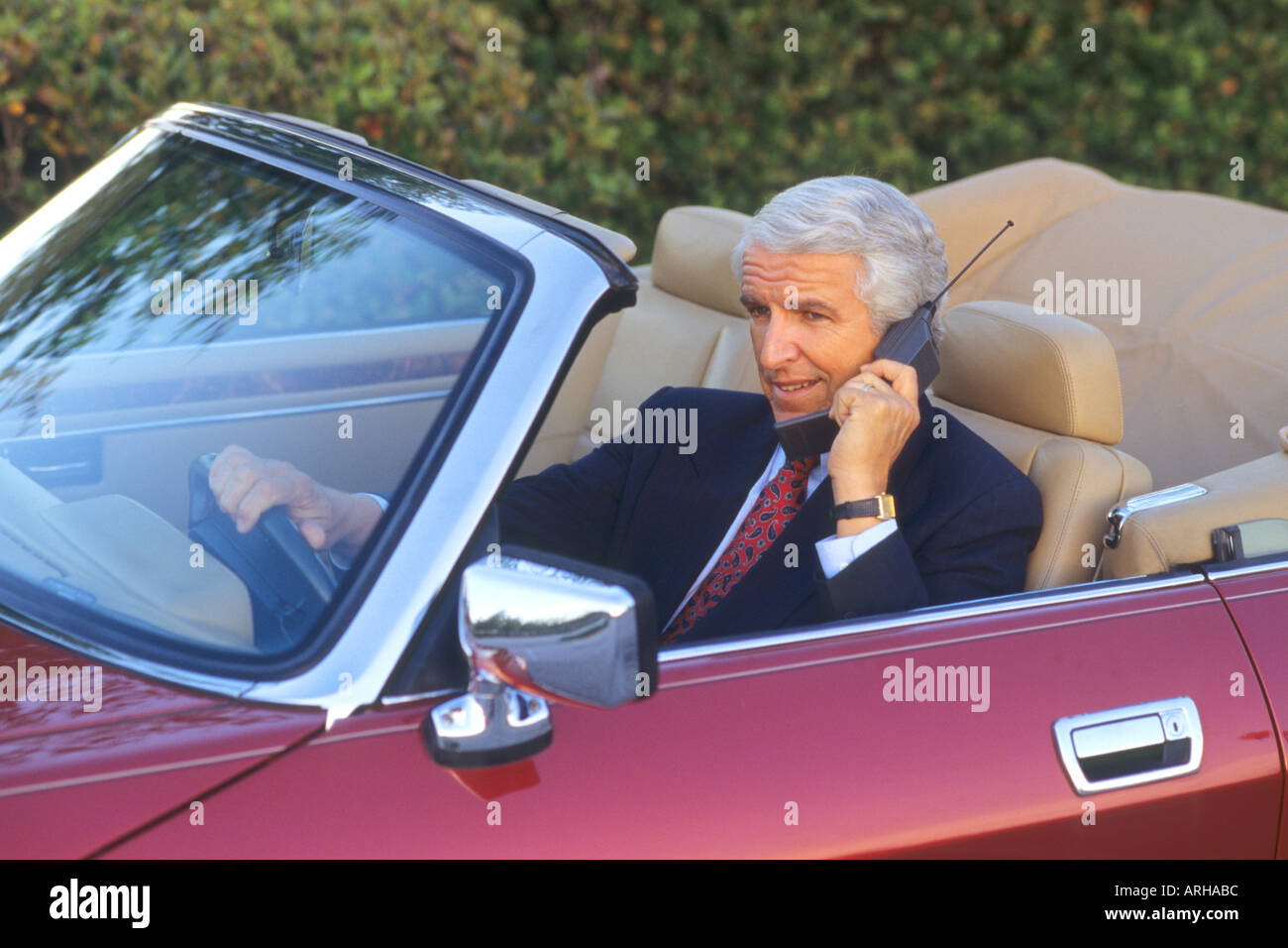 Businessman on global satellite phone in convertible - Stock Image