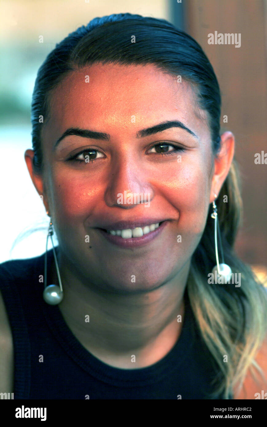 YOUNG TURKISH WOMAN IN HER EARLY TWENTIES SMILING POSITIVELY,TURGUTREIS,TURKEY - Stock Image