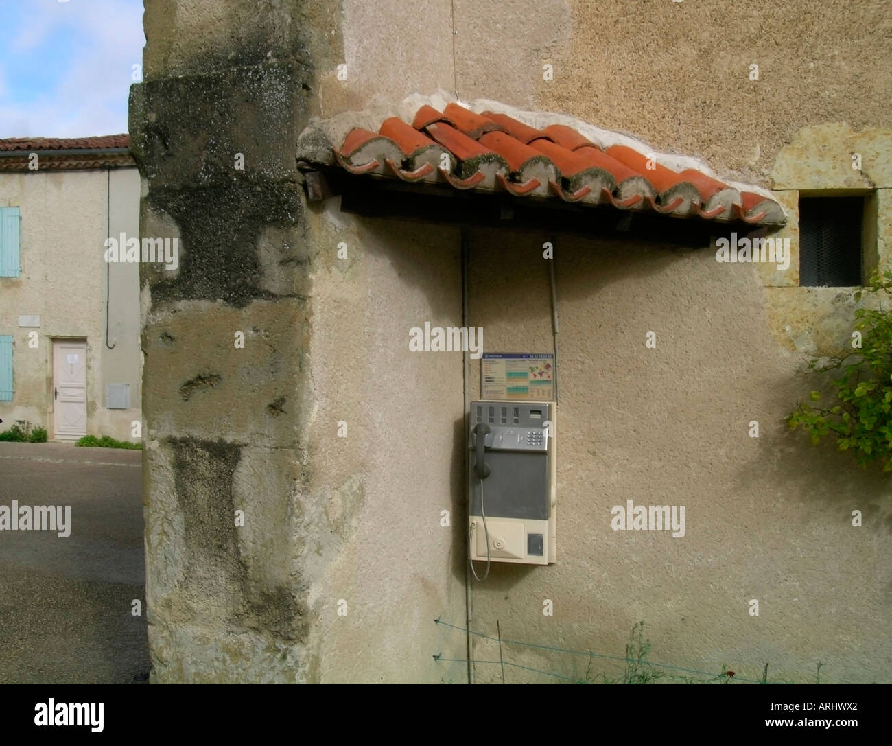 public telephone under a little roof made of tiles at an old house wall in southern France - Stock Image