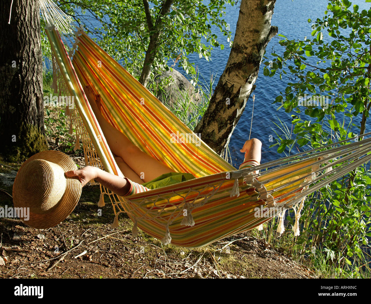 woman lying in a yellow hammock on the lakefront with birches Stock Photo