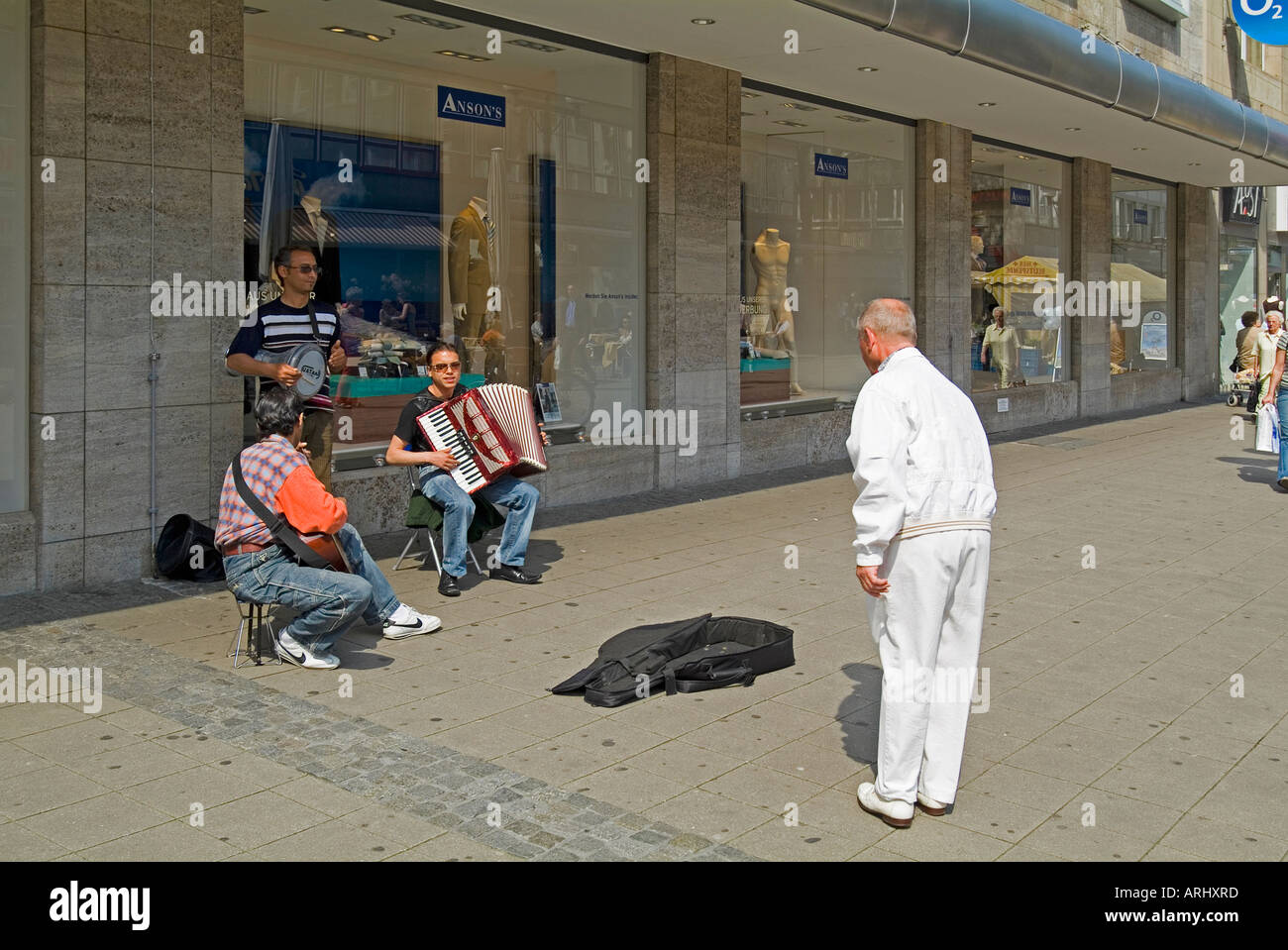 man listening to street musicians on the pedestrian area Kettwiger Strasse Street in Essen Germany - Stock Image