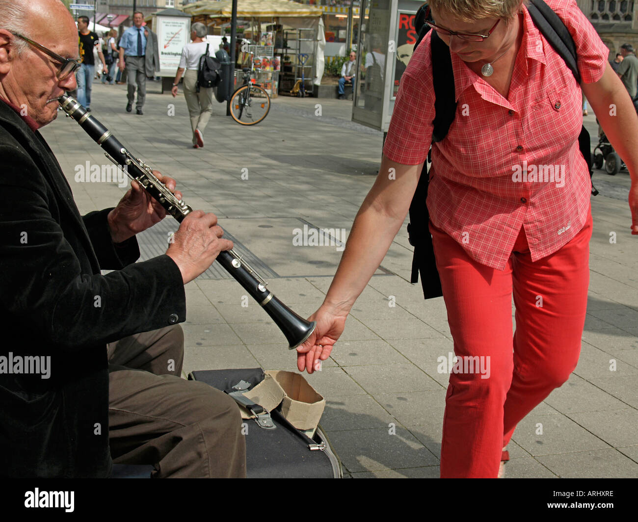 woman giving money to a street musician on the pedestrian area Kettwiger Strasse Street in Essen Germany - Stock Image
