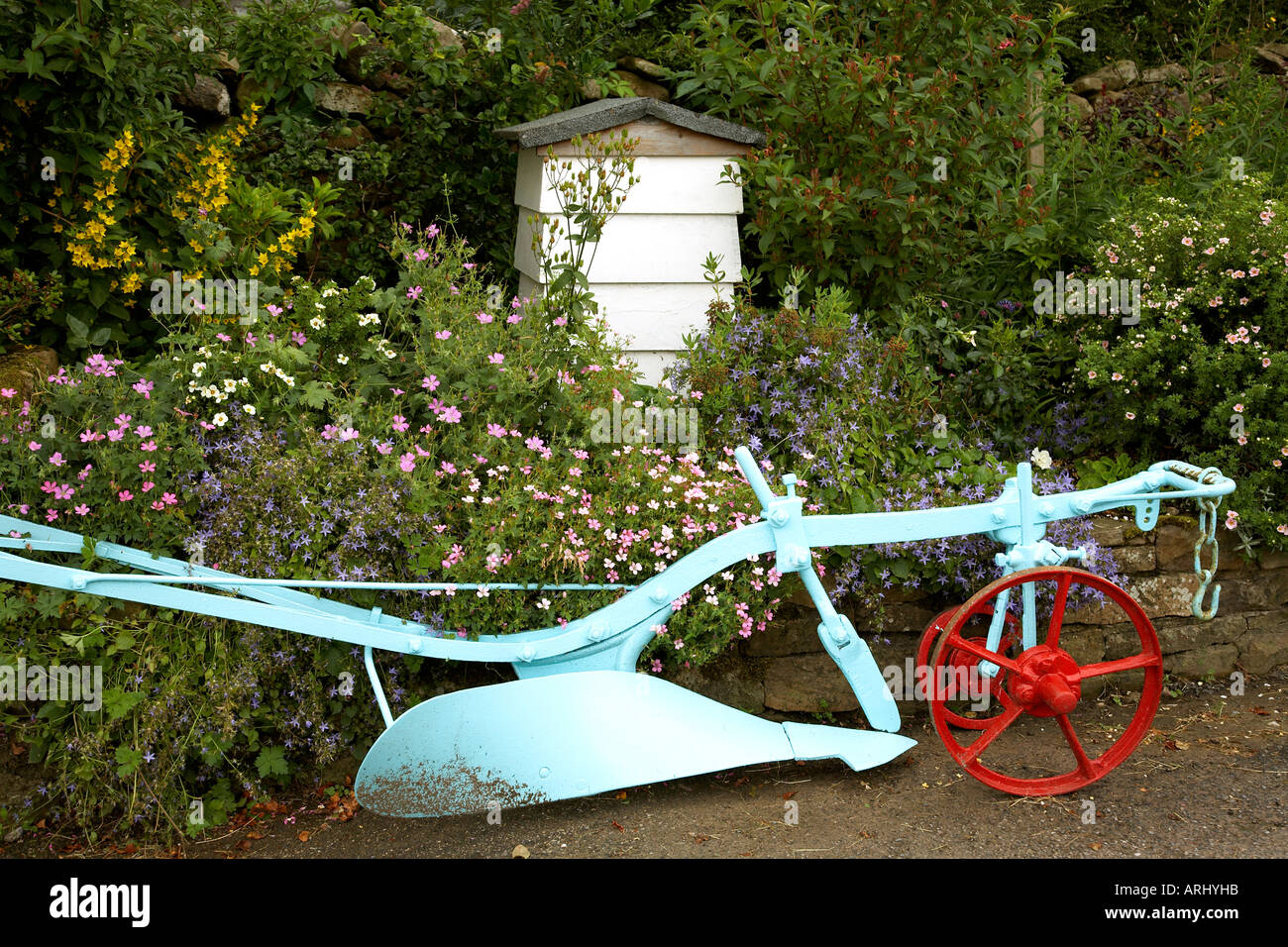 A white beehive and an old plough with the wheel painted red used as a feature in a garden in Dent in the Yorkshire Dales National Park - Stock Image