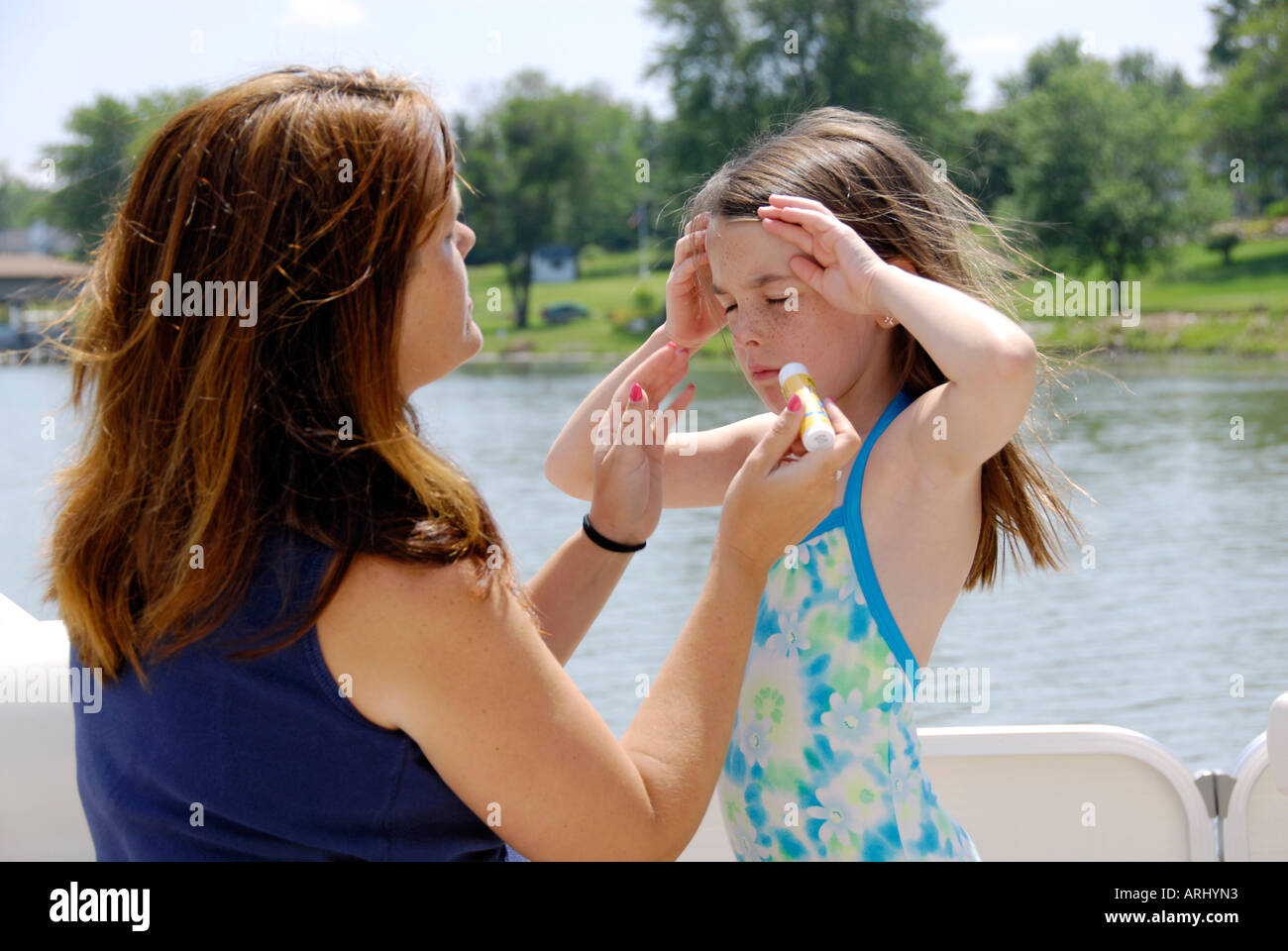Mother applies sun screen to her daughters face to protect her from UV radiation from the sun and sunburn - Stock Image